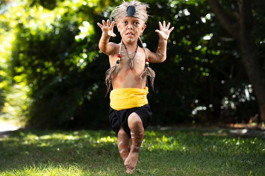 A young indigenous boy with a form of dwarfism dances in traditional dress. He looks to the camera with his palms spread.