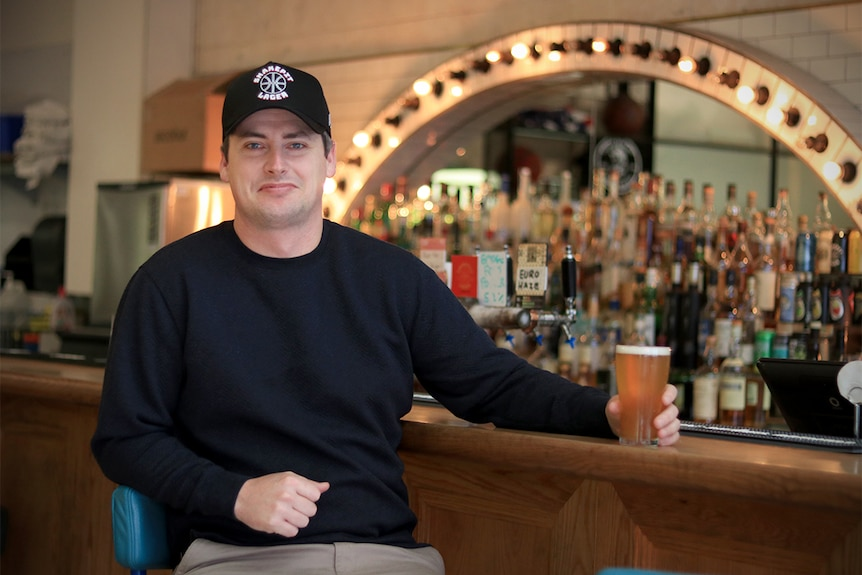 Lachlan Stevens sits at a bar wearing a black shirt and hat while holding a beer.