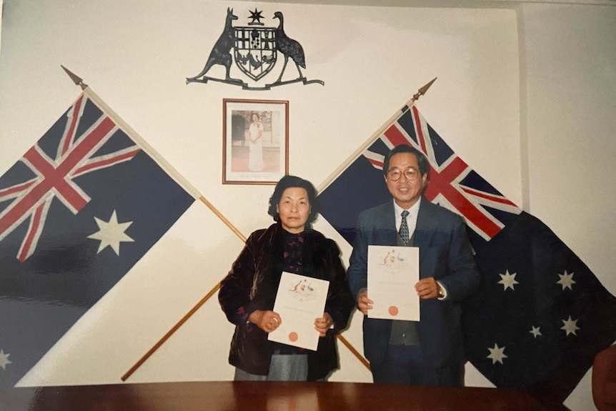 Two well dressed Asian people stand in front of Australian flags.