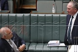 Scott Morrison watches Barnaby Joyce speaking at the lectern in parliament.