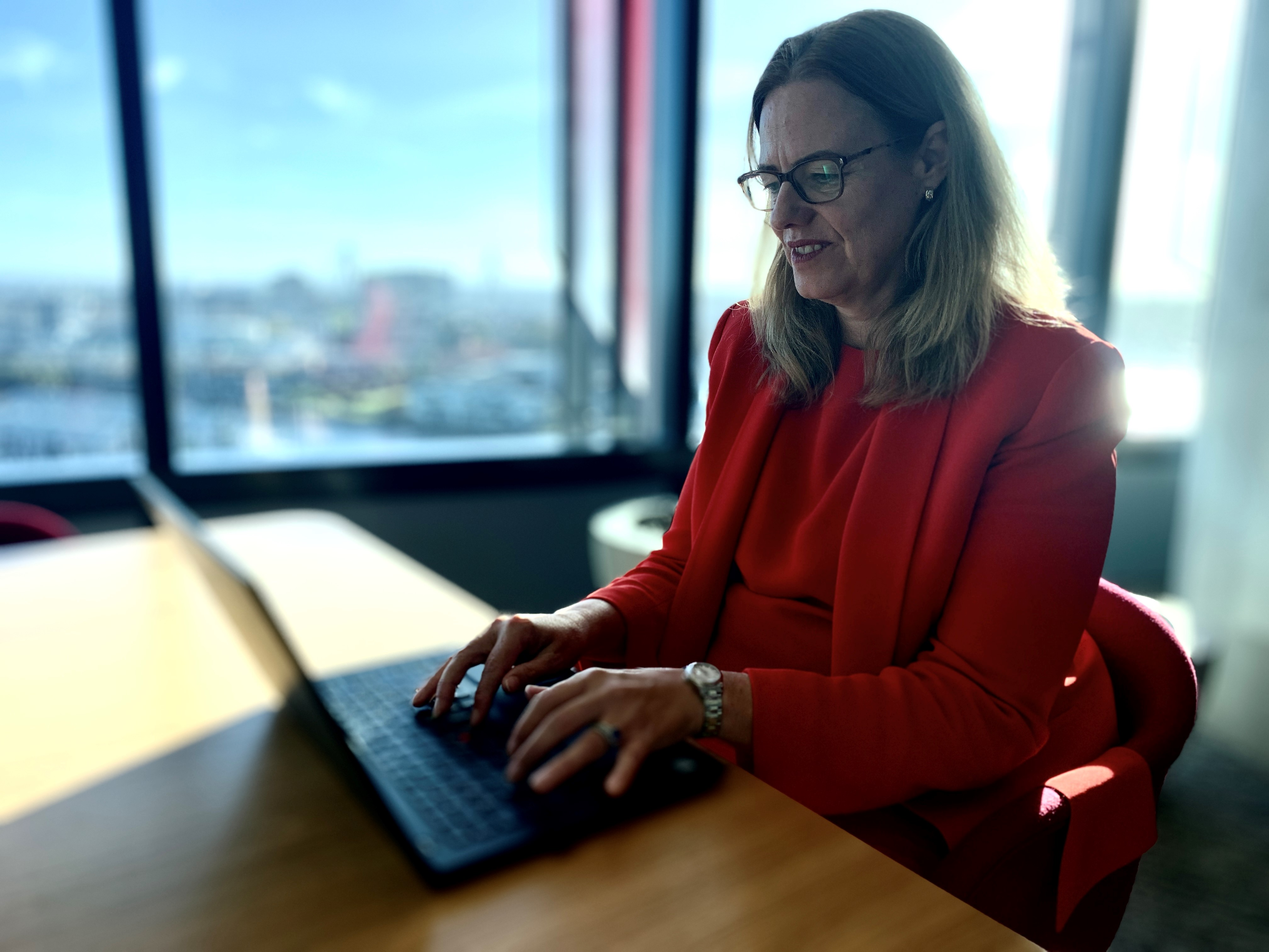 A woman in a red suit types on a laptop