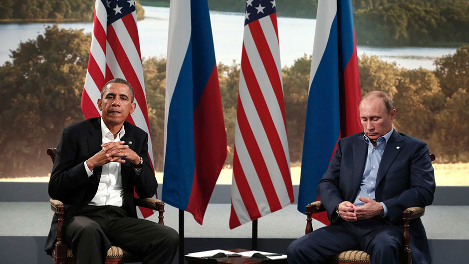 Barack Obama and Vladimir Putin looking glum while sitting in chairs before a row of US and Russian flags
