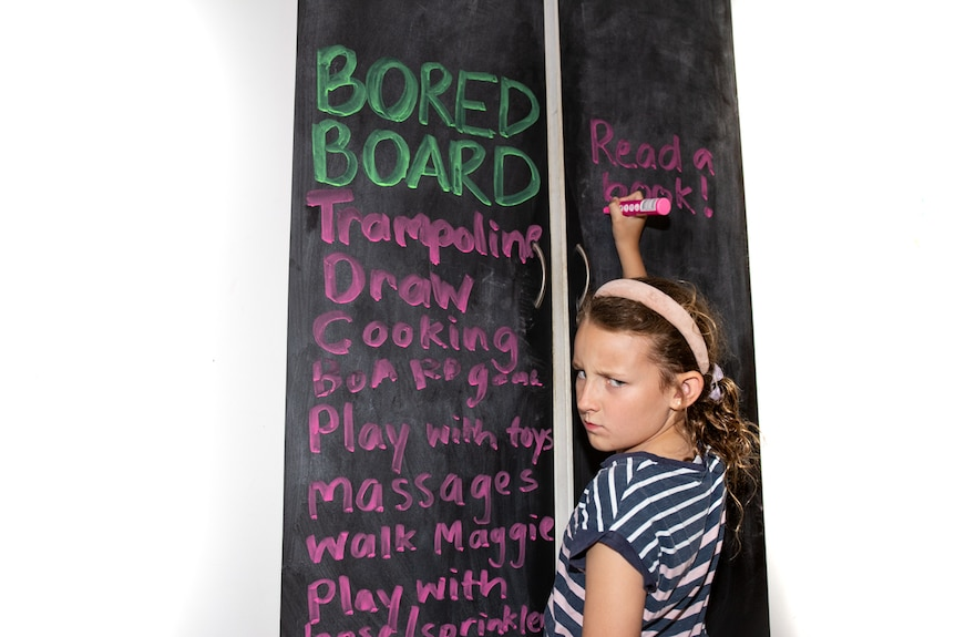 Girl writing a list of activities that don't involve screens in a story about reducing screen time to engage with kids.