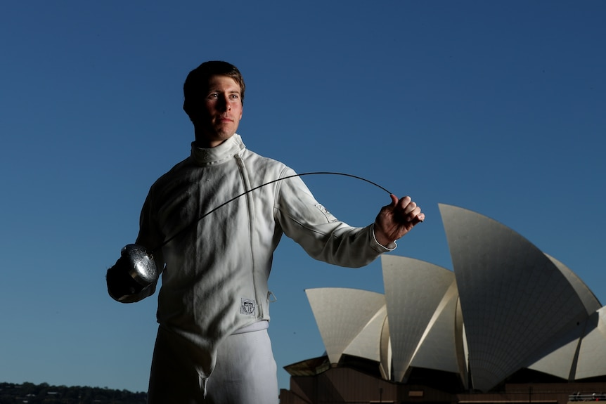 Edward Fernon poses with a fencing sword with the Opera House in the background..