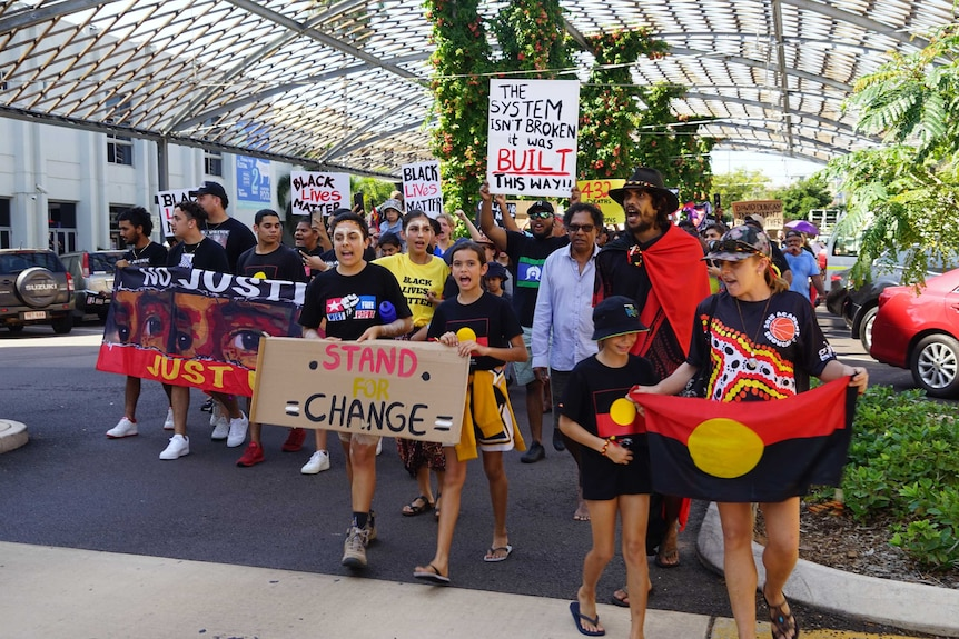 People are holding signs saying 'Black Lives Matter' as they march through Darwin City.