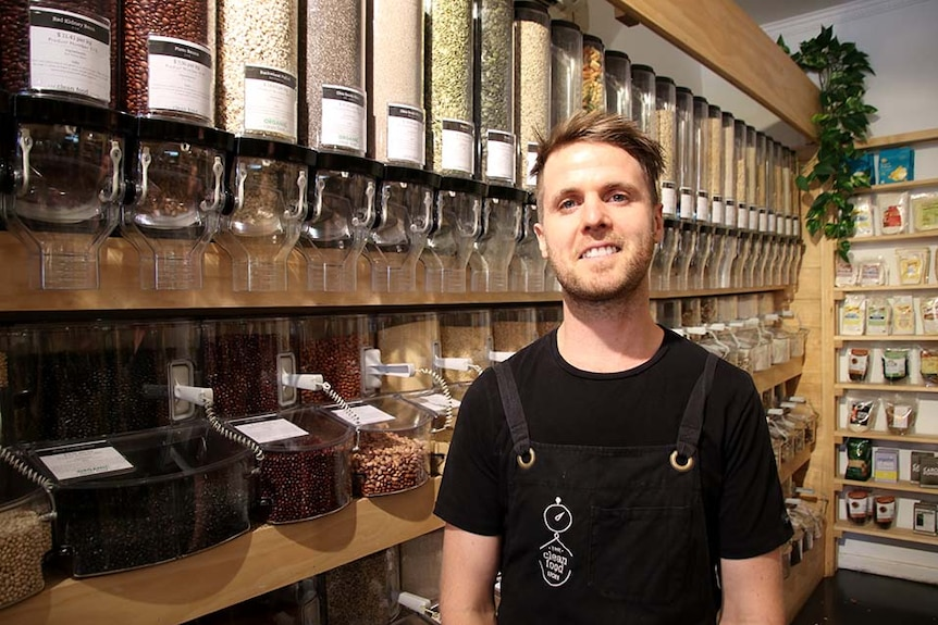 A man wearing an apron stands in a store selling whole foods, nuts and beans etc.
