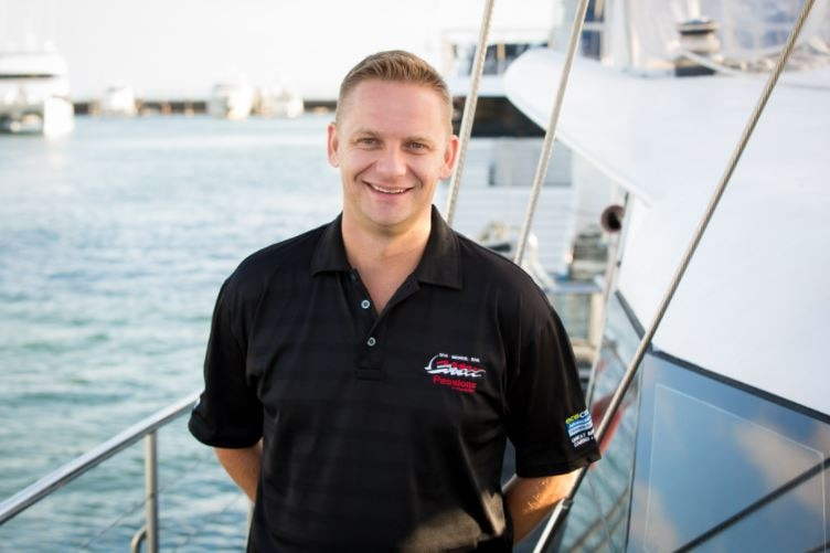 A man smiles, stands by a boat at a marina