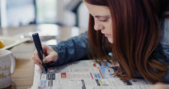 Seorang perempuan sedang mencari kerja di koran
