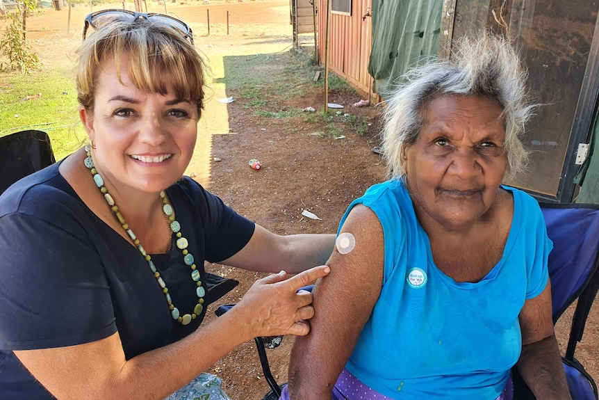 Two women sitting next to each other, with one pointing to the vaccine mark on the other's arm.
