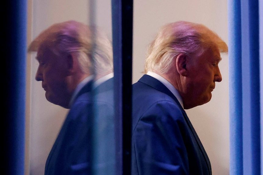 A side on profile of Trump looking downcast is reflected behind him