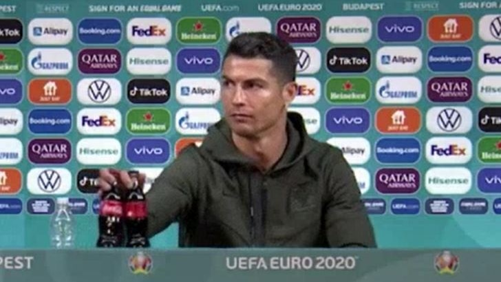 Cristiano Ronaldo moves two bottles of Coke at a staged press conference.