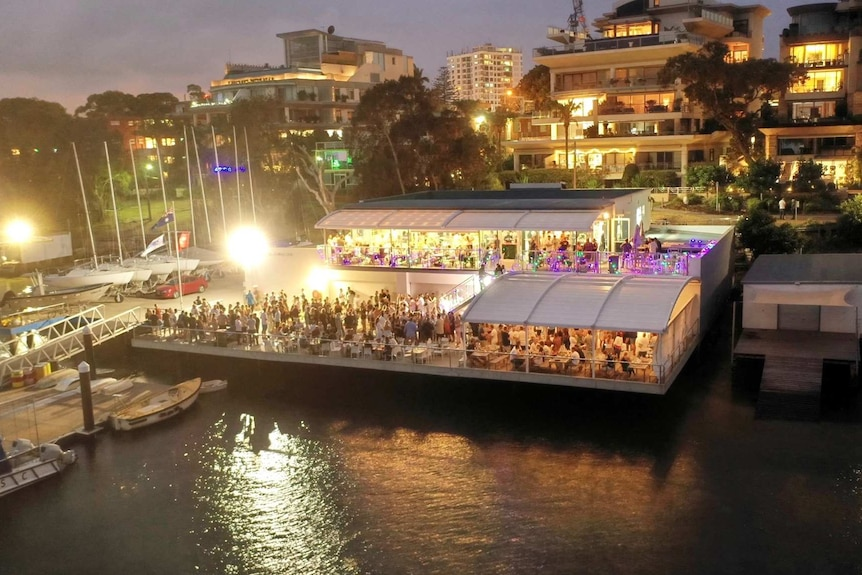 Wide shot of Cronulla Sailing Club at night with people in the club and on the deck overlooking the water