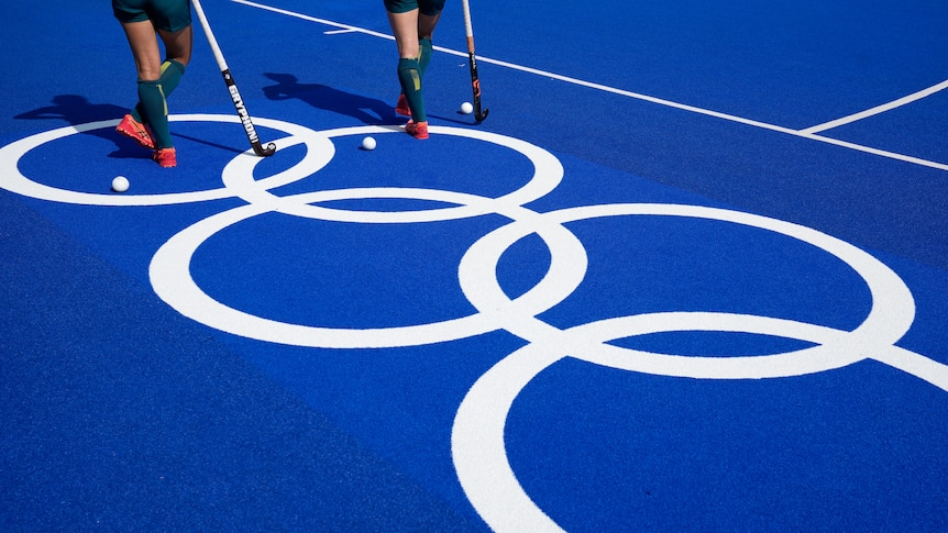 Two sets of legs standing with hockey sticks on a blue training field with the olympic rings in large white print.