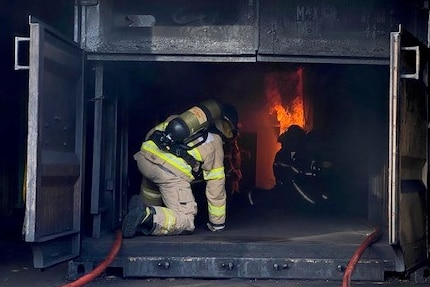 Firefighters sit inside a black box with flames in it