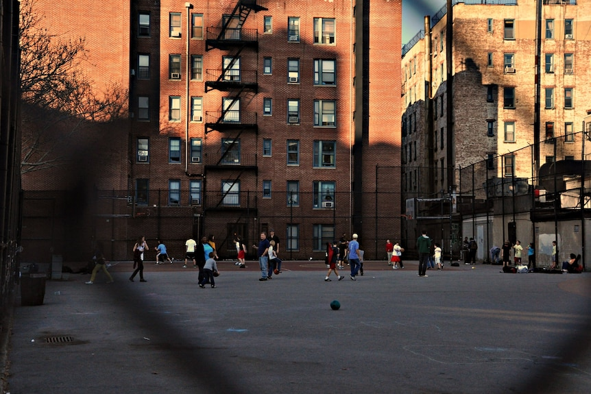 A wide shot shows a neighbourhood basketball court with lots of players and big buildings in the background.
