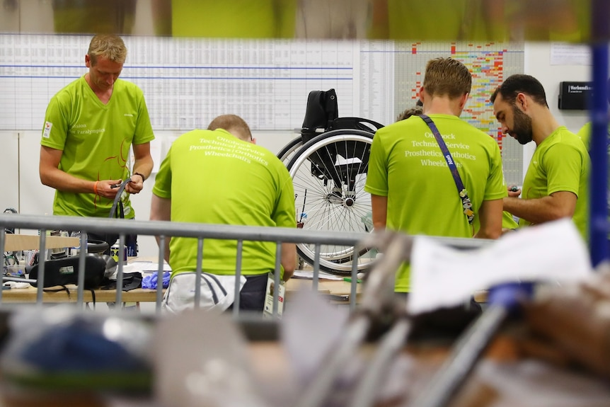 A group of technicians dressed in lime green T-shirts repairing Paralympic Games equipment and personal aids