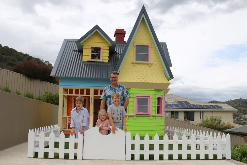 A man stands with his three children in the front yard of a massive cubby house.