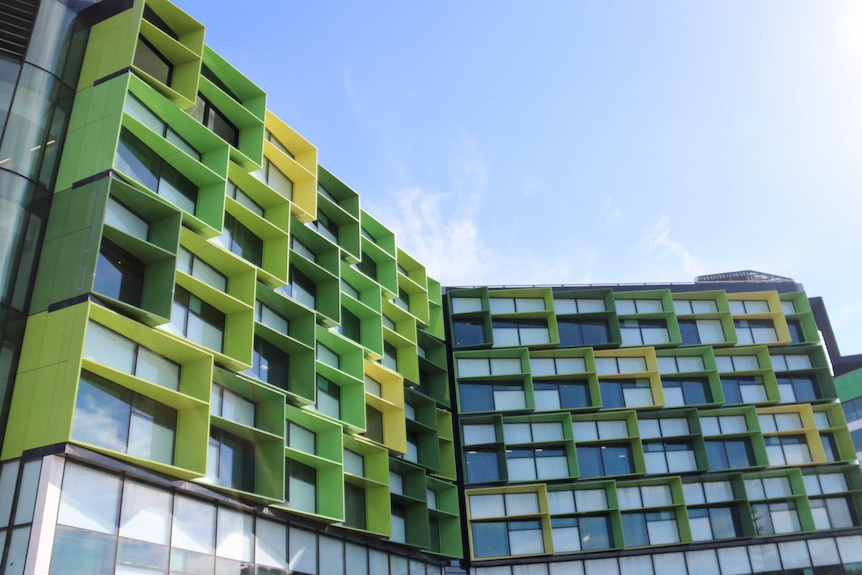 A picture of the exterior of Perth Children's Hospital, showing distinctive green-panelled window frames under a blue sky.