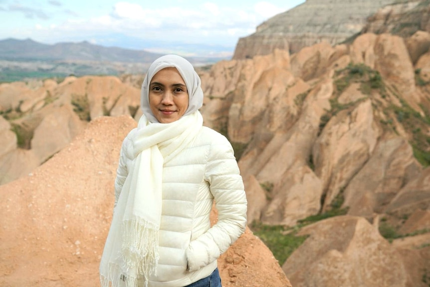 A woman wearing hijab standing in front of rocky hills