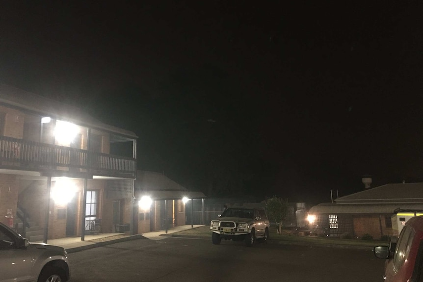 A motel in night-like darkness caused by smoke. Only building lights show the motel's car park.