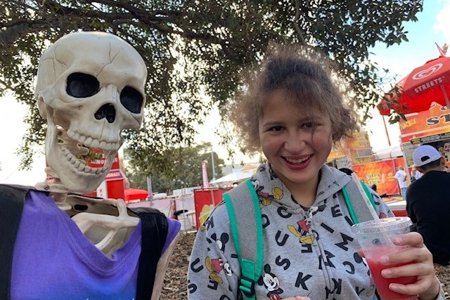 A skeleton in a purple shirt and a girl with brown hair and a slushee, smiling at the camera.