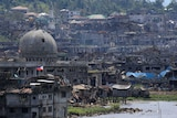 A wide shot of damaged buildings beside a mosque in Marawi city.