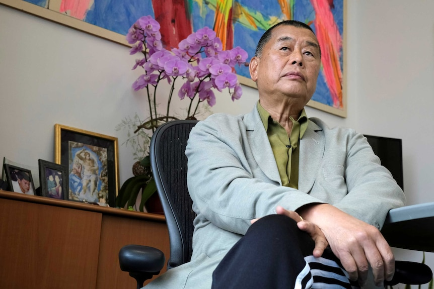 A man in a green shirt and grey blazer sits looking contemplative in front of a colourful painting and potted orchid