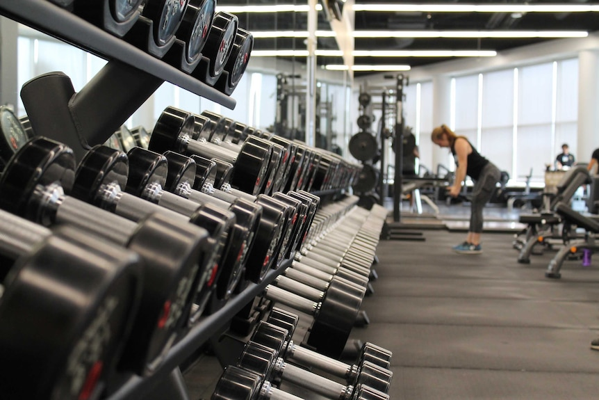 A rack of weights in a gym is in focus while a woman lifts dumbbells in the background