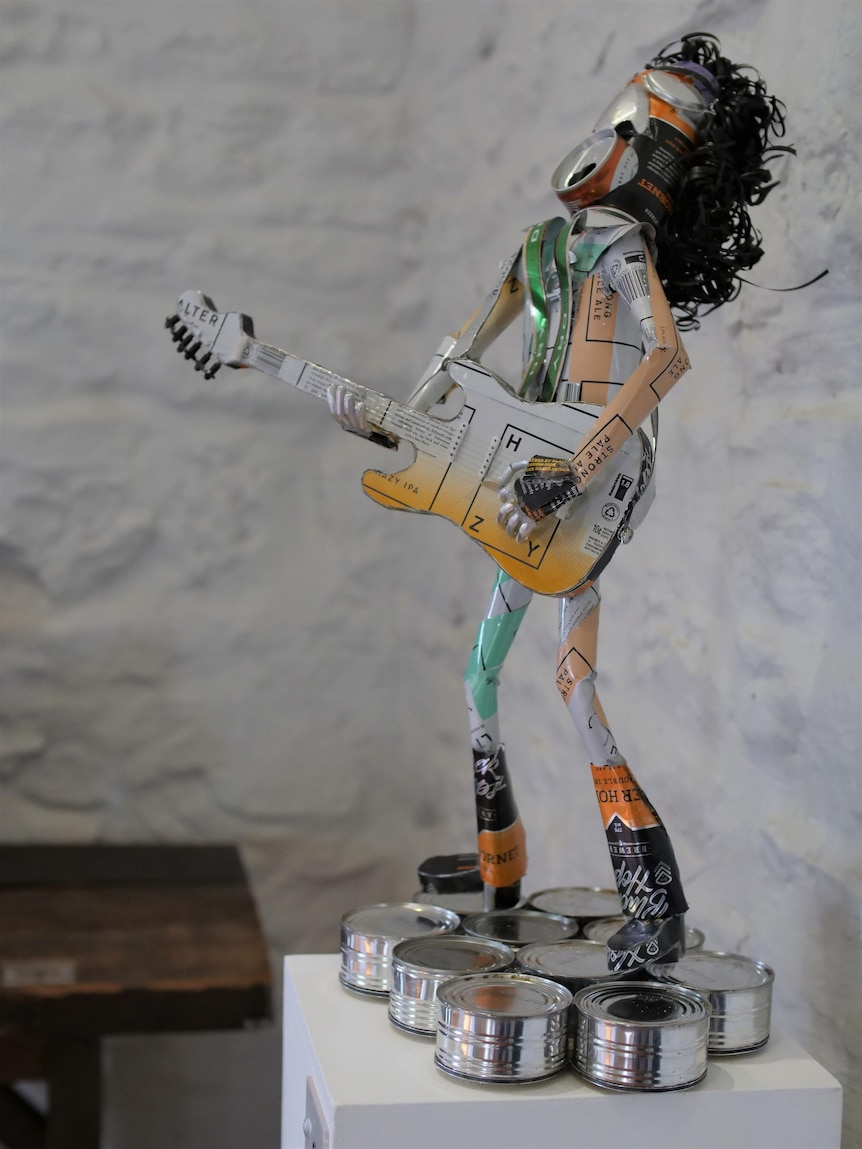 A rock star sculpture made from aluminium cans, standing on a collection of shortened tin cans.