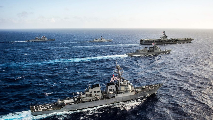 Ships from the US and Indian navies, and Japan Maritime Self-Defense Force transit in formation.