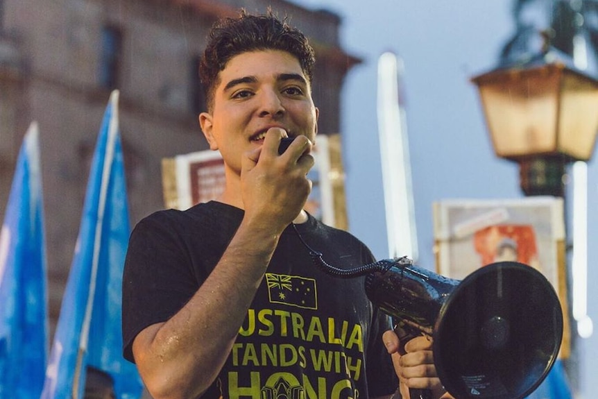 UQ philosophy student Drew Pavlou speaks at a rally with a megaphone.