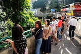 A long queue of people stretches down a pathway on a main road as they wait to vote in Hong Kong.