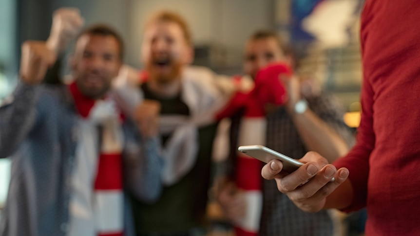 A man distracted by his phone while his friends enjoy a sporting match behind him.