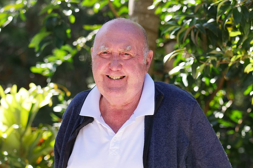 elderly man with with white shirt and blue zip up jumper smiles at the camera.