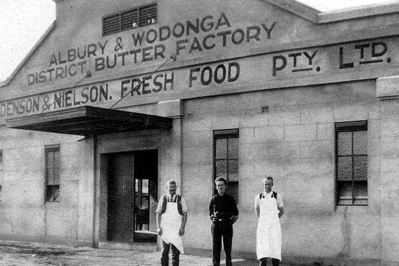 Black and white image of three male workers standing in front of the Holdenson and Nielson Fresh Food dairy company building