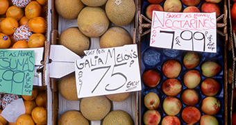 """A sign for """"melon's"""" at a greengrocer."""