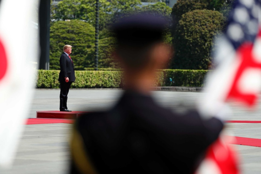 Donald Trump stands no a red platform with a Japanese and US flag in the foreground.