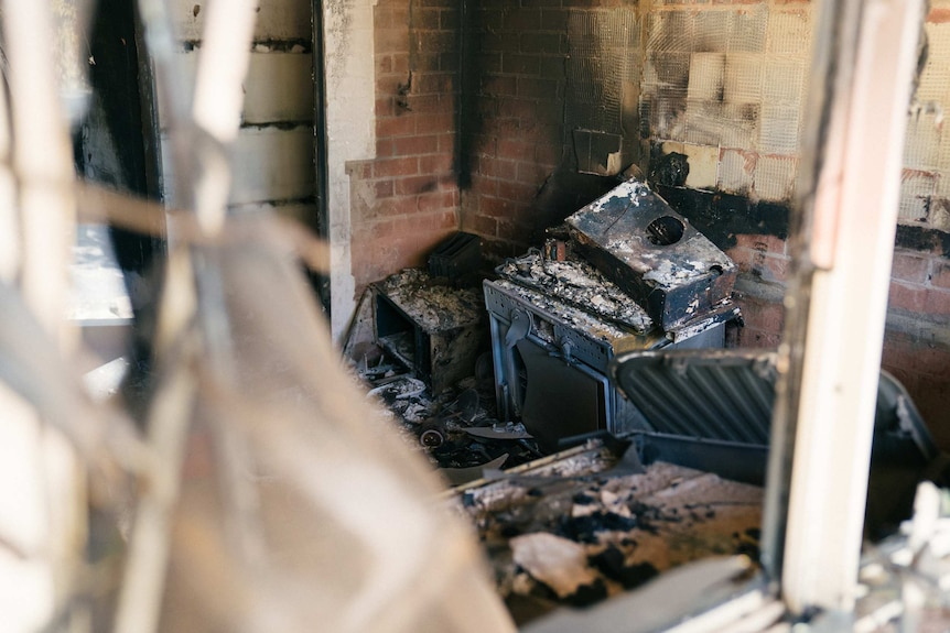 An oven or possibly a washing machine lies burnt and melted up against a wall.