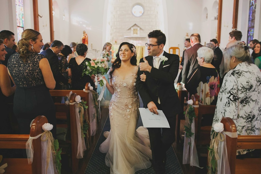 Nas and Tom walk up the aisle after their wedding ceremony, smiling and among friends and family