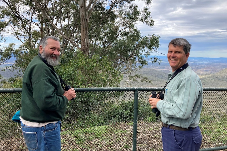 Two men with binoculars standing on a hill overlooking bushland and smiling.