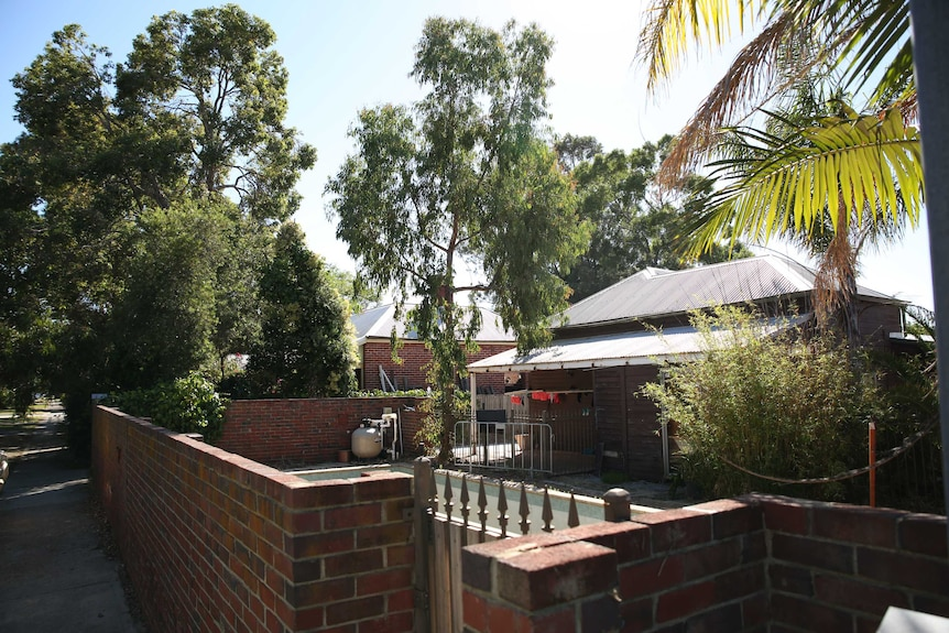 The front yard of a tin roof and brick house. Trees and a bbq in the yard.