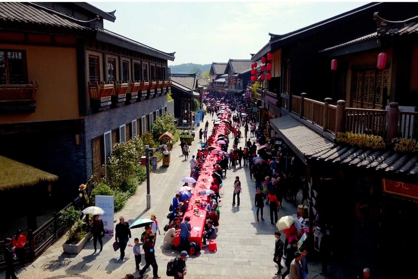a long red table runs through the streets of a chinese town