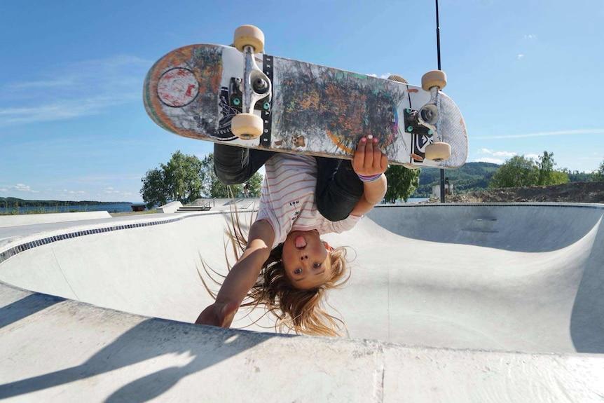 Sky Brown holds herself upside down on a skateboard.