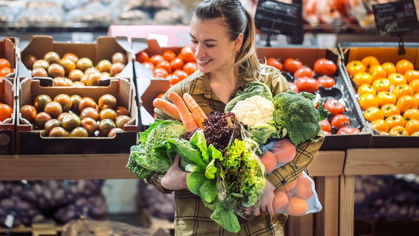 Woman in grocery store with an armful of vegetables including carrots, lettuce, cauliflower, and broccoli.