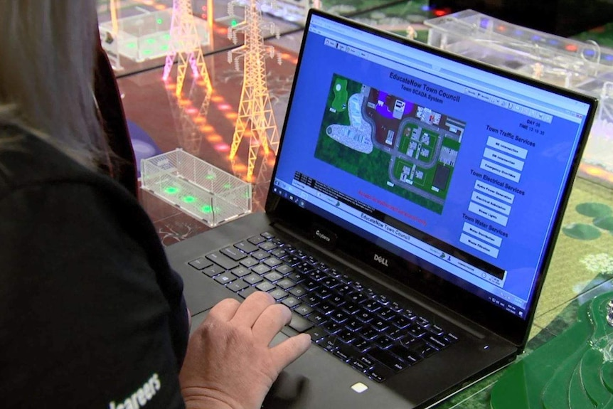 """A laptop that says """"EducateNow Town Council"""" on a table that shows bright lights and power lines."""
