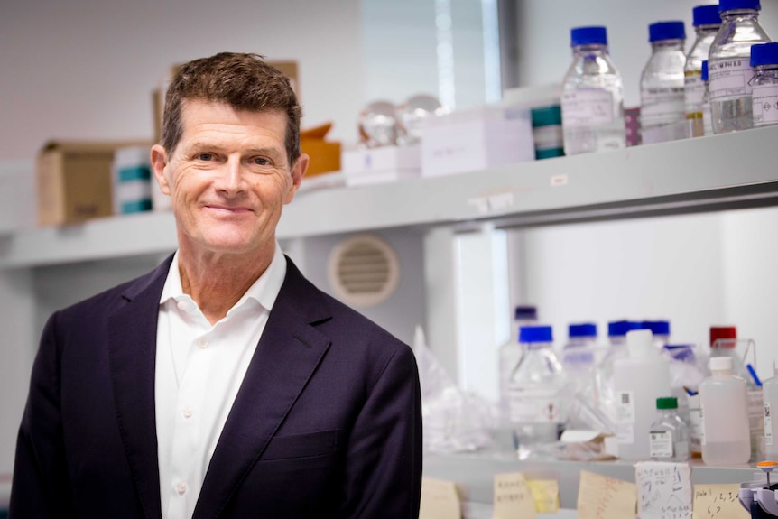 Lead scientist Professor Chris Goodnow stands in the laboratory at the Garvan Institute with bottles in the background.