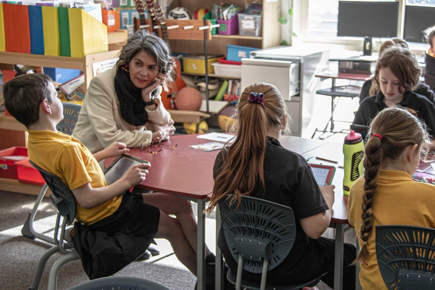 Female teacher sitting with Indigenous students at a desk