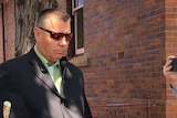 man with sunglases, brown suit and green shirt walking outside a building