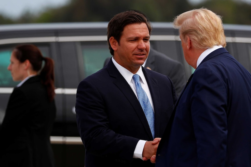 Ron DeSantis smiles and shakes hands with Donald Trump