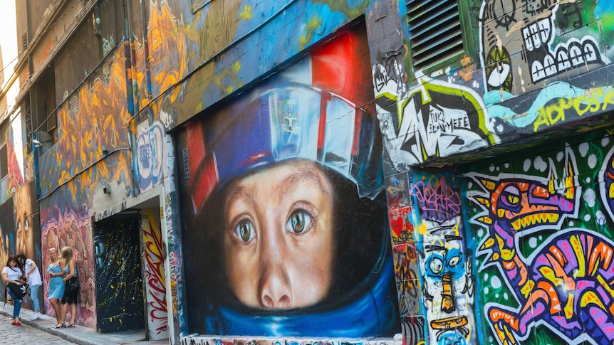A large wall painted brightly with different words and images, and the large head of a child wearing a helmet at the centre